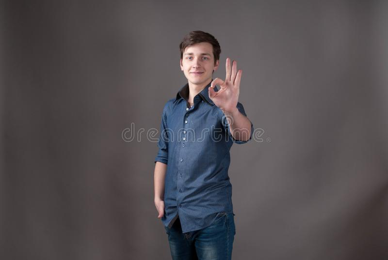 Young man in blue looking at camera and showing okay sign. Handsome young man in blue looking at camera and showing okay sign with hand on grey background with stock photo