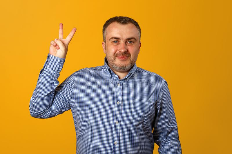 A young man in a blue plaid shirt shows a victory sign and looks at the camera. Yellow background. Close-up stock photo