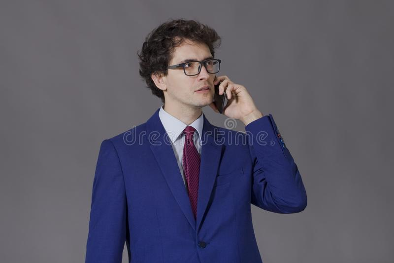 Businessman at work. Young man in blue suit and glasses standing and talking by mobile phone royalty free stock photography