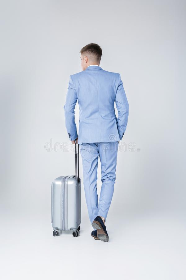 Young man in blue suit with suitcase. Handsome elegant young man in blue suit stands with his back with suitcase against grey background stock images