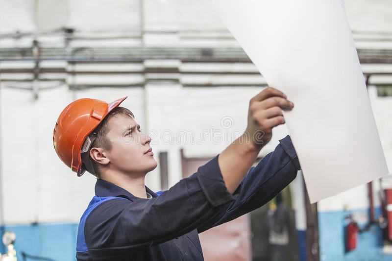 Young man with blueprints working on an old factory for the inst. Allation of equipment protective helmets royalty free stock image