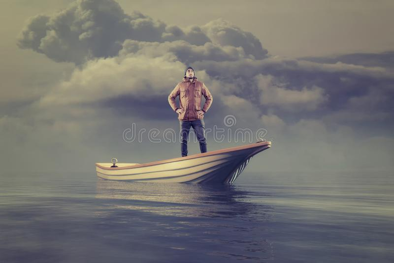 Young man in a boat at sea. Looking up to the horizon stock image