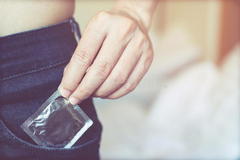 Young man body Take off shirt. jeans front side pocket to carry condoms taking in hand condom from jeans royalty free stock photo