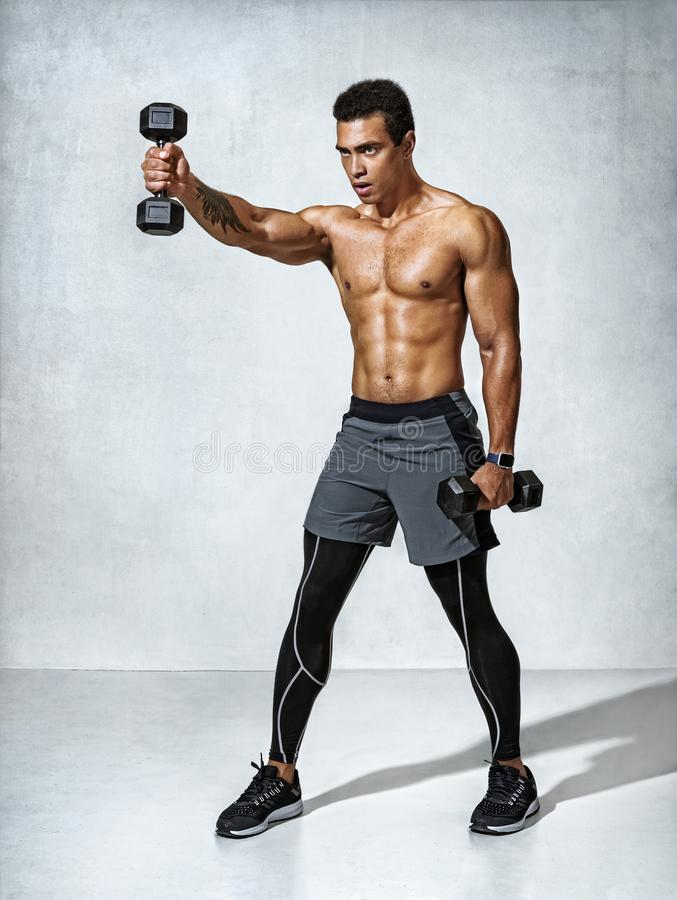 Young man bodybuilder doing exercise with heavy weight dumbbells stock images