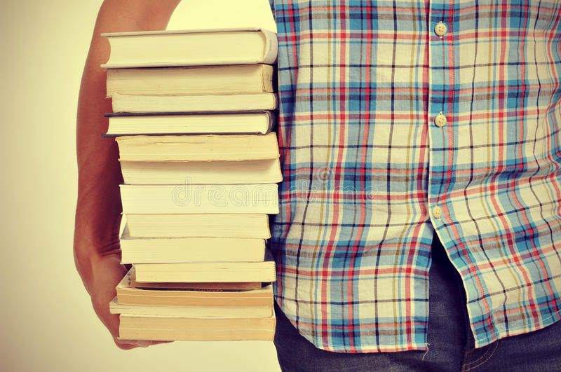Young man with books, with a filter effect. Closeup of a young man holding a pile of books, with a filter effect royalty free stock images