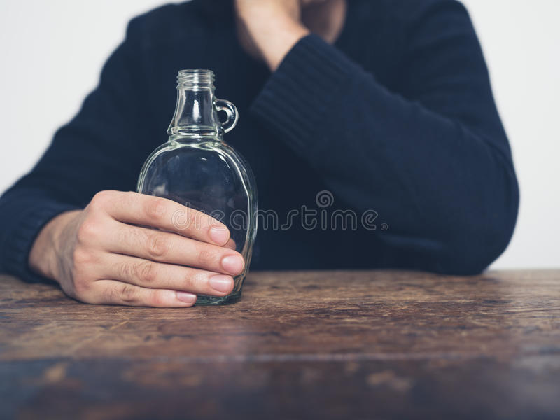 Young man with bottle at table royalty free stock photo