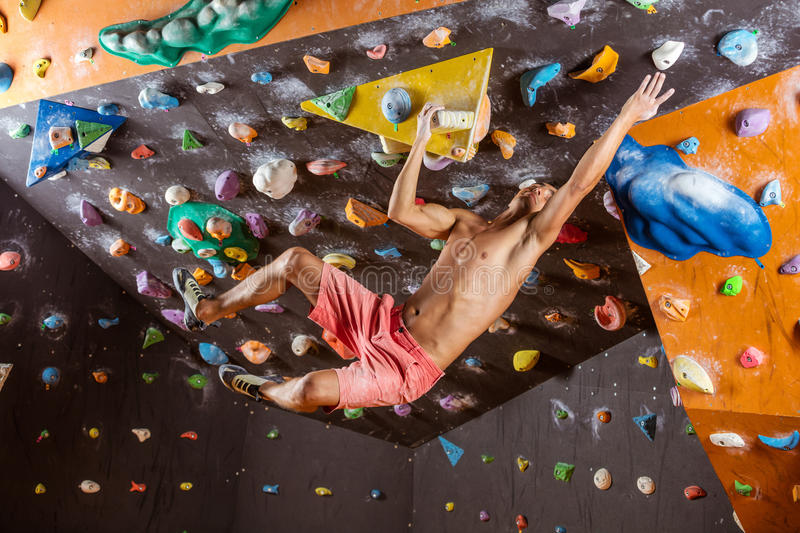 Young man bouldering in indoor climbing gym. Trying to reach next handhold royalty free stock photography