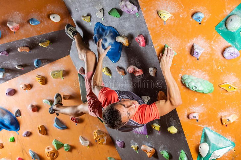 Young man bouldering in indoor climbing gym. Trying to solver challenging problem royalty free stock images