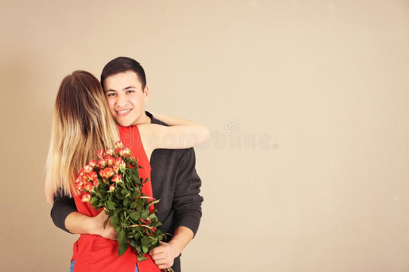 Young man with bouquet of flowers hugging his girlfriend on color background royalty free stock photography