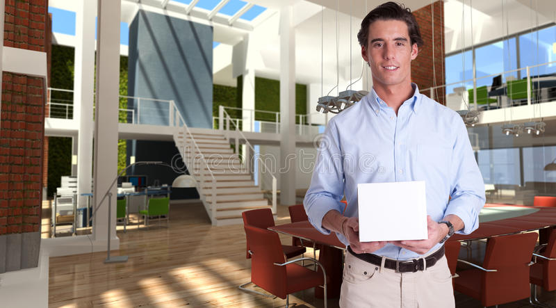 Young man with a box in a modern office. Cheerful young man holding a white box in a modern luxurious office royalty free stock photos
