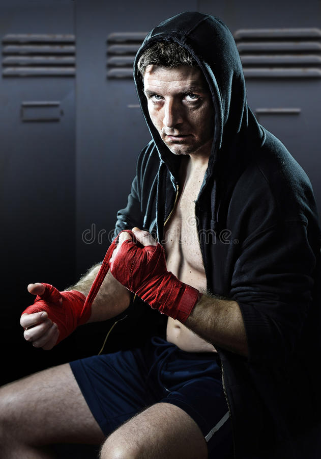 Man in boxing hoodie jumper with hood on head sitting wrapping hands and wrists getting ready for fighting. Young man in boxing hoodie jumper with hood on head stock photography
