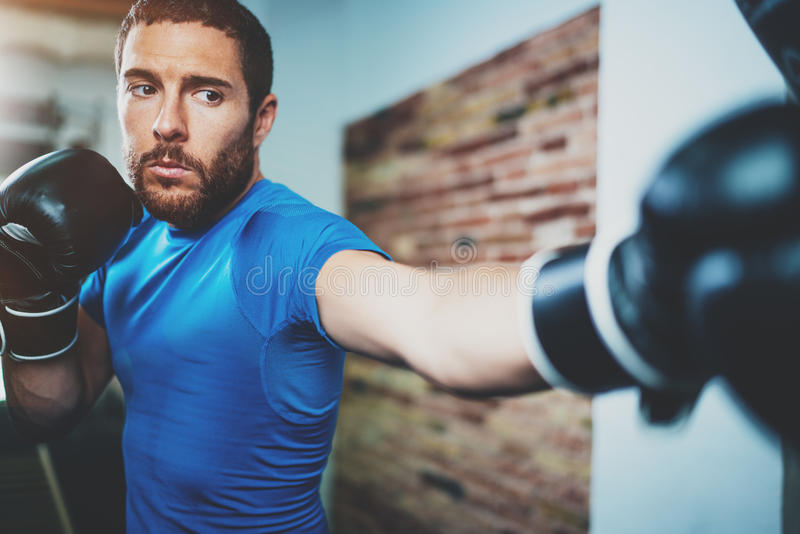 Young man boxing workout in fitness gym on blurred background.Athletic man training hard.Kick boxing concept.Horizontal. Young man boxing workout in fitness gym royalty free stock image