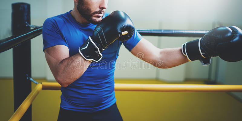 Young man boxing workout on ring in a fitness club. Caucasian male boxer in black gloves. Muscular strong man on royalty free stock images