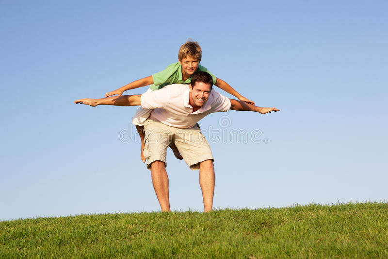 Download Young Man With Boy Playing In A Field Royalty Free Stock Images - Image: 17061079