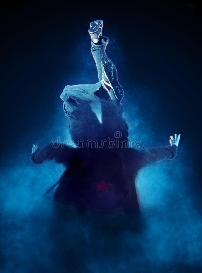 Young man break dancing on dark smoke background royalty free stock image