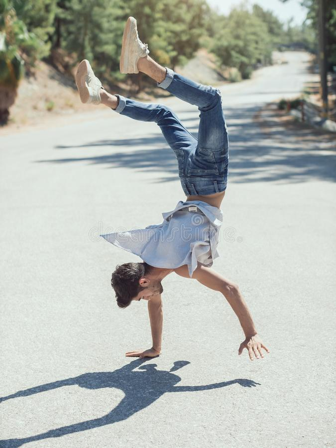 Young man break dancing on the road. stock photography