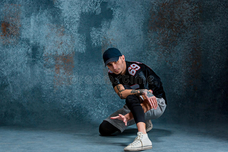 Young man break dancing on wall background. royalty free stock photos
