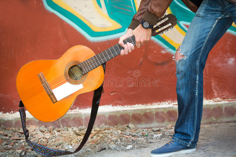 Young man breaking a guitar on the floor stock photos
