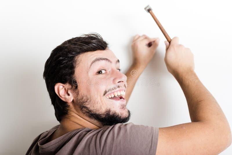 Young man bricolage hammering nail wall. At home royalty free stock photography