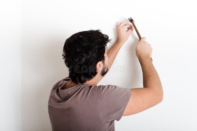 Young man bricolage hammering nail wall. At home royalty free stock image