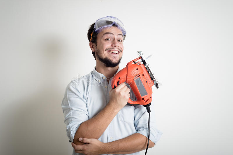 Young man bricolage working with electric saw. At home stock photo