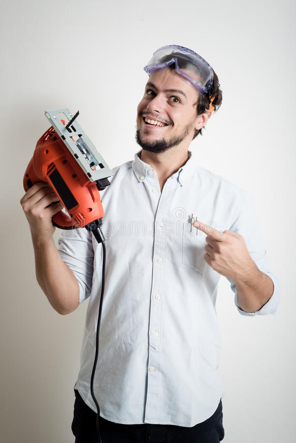 Young man bricolage working with electric saw. At home royalty free stock image