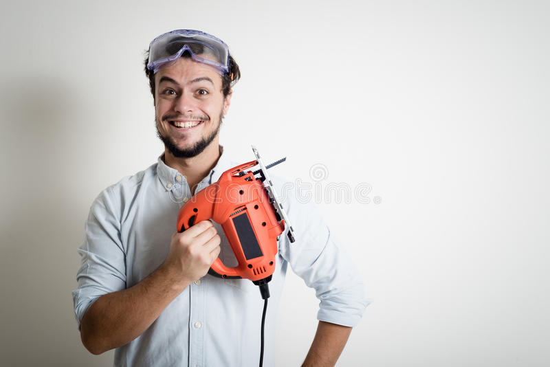 Young man bricolage working with electric saw. At home stock photography
