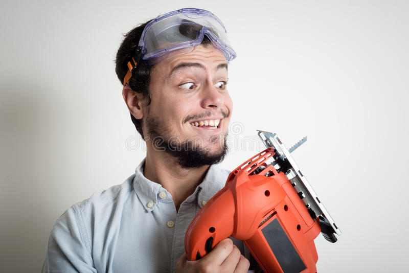 Young man bricolage working with electric saw. At home royalty free stock photo