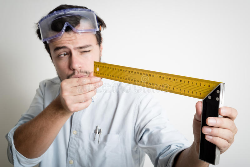 Young man bricolage working measuring with meter. At home royalty free stock photography
