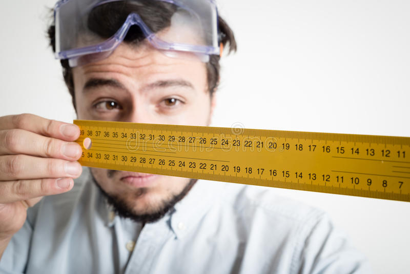 Young man bricolage working measuring with meter. At home stock photo