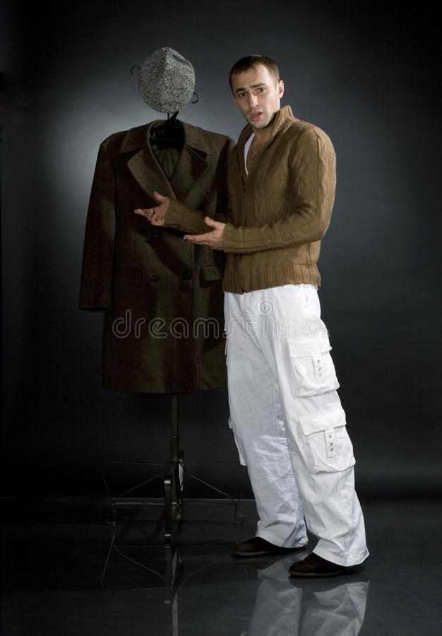 Young man in a brown jacket. And white trousers stock image