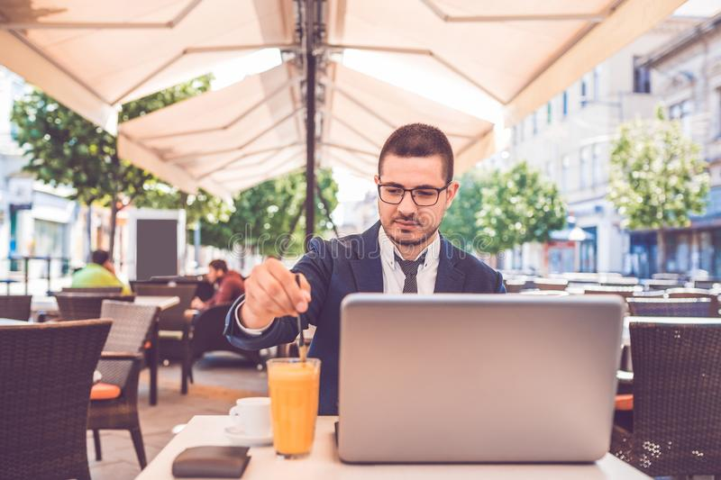 Young man browsing internet on his laptop and drinking juice in the city stock images