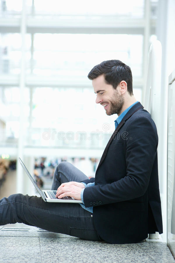 Young man browsing the internet on laptop royalty free stock images
