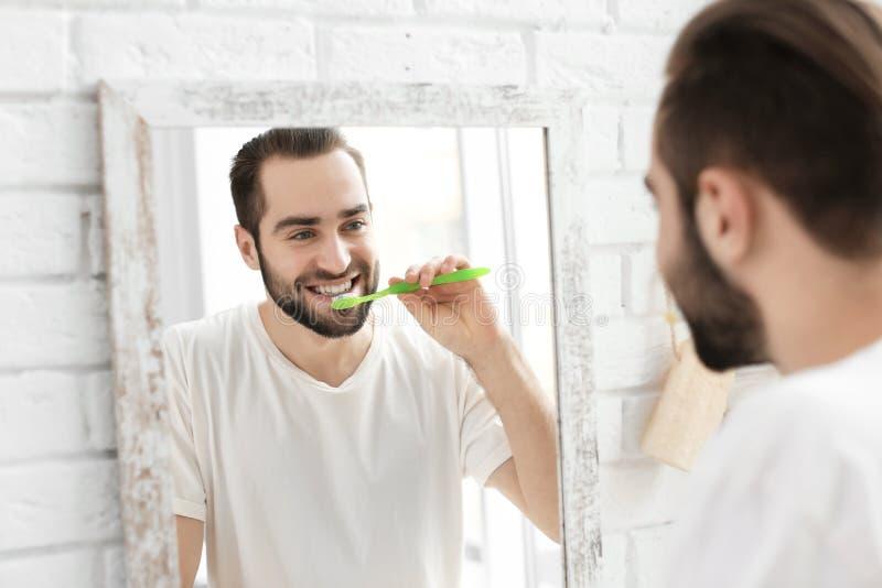 Young man brushing his teeth. In bathroom stock image