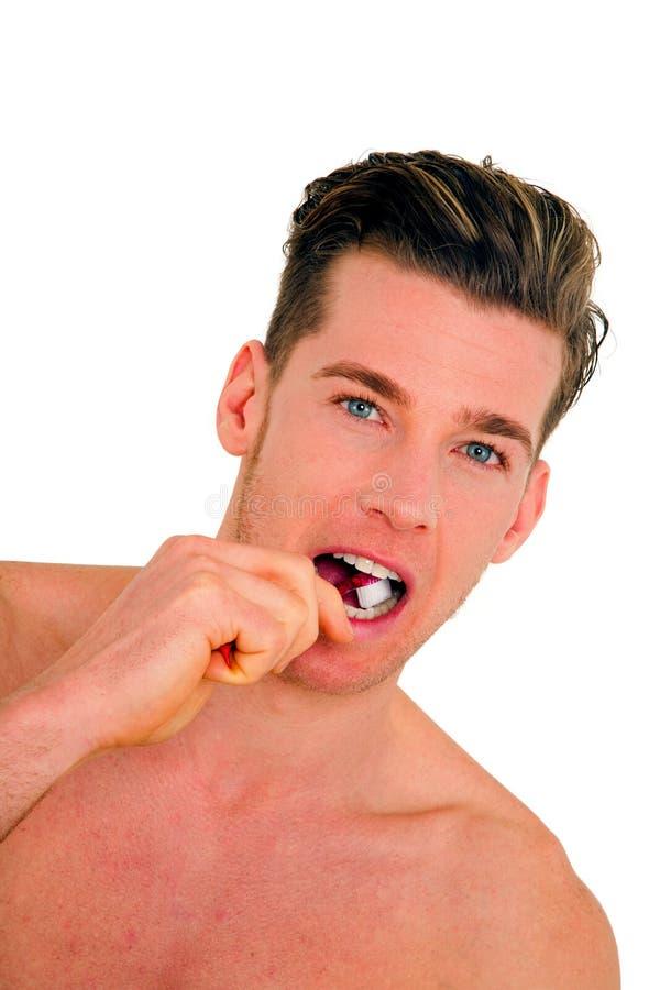 Young man brushing his teeth royalty free stock photo