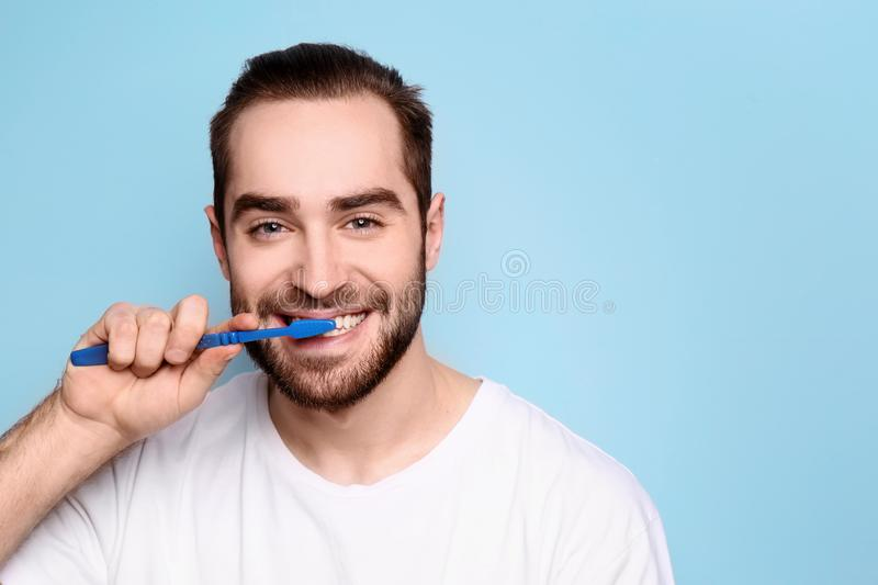 Young man brushing his teeth. On grey background stock images