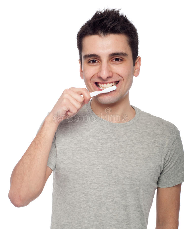 Young man brushing teeth. Handsome young man brushing his teeth with toothbrush (isolated on white background stock photography