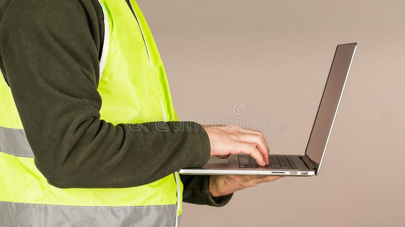 A young man, a Builder in the green safety vest, using a computer, on a gray background. Technology in industrial works.  royalty free stock photo