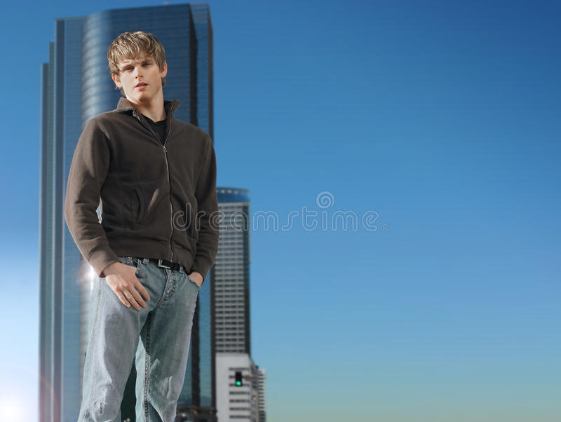 Young man and building with sky. Young man standing outdoors against background of empty blue sky and modern building stock photo