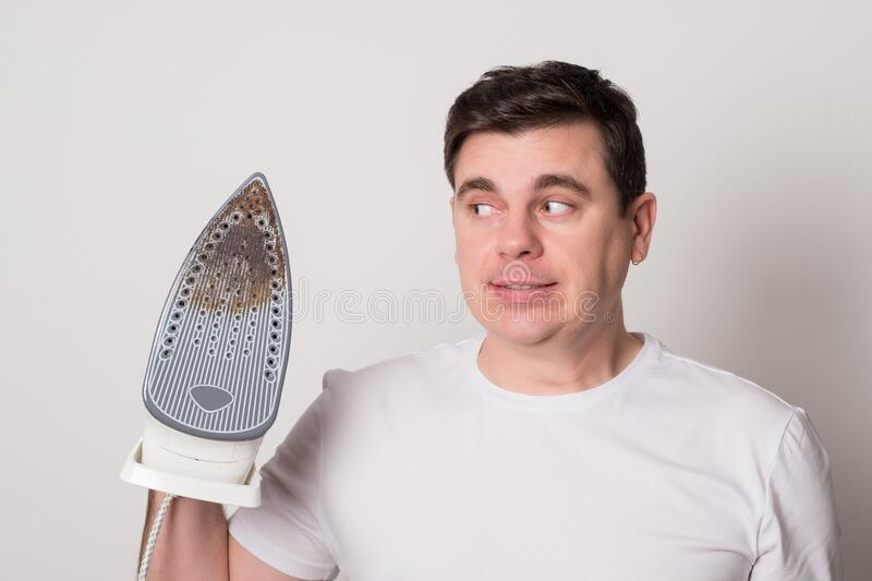 Man burned clothes with an iron. Positive man with a broken iron. Young man burned clothes with an iron. Positive man with a broken iron royalty free stock photos