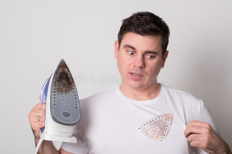 Young man burned clothes with an iron. Positive man with a broken iron stock photos