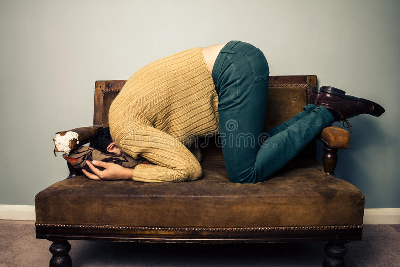 Young Man Burying His Face In Old Sofa Royalty Free Stock Image