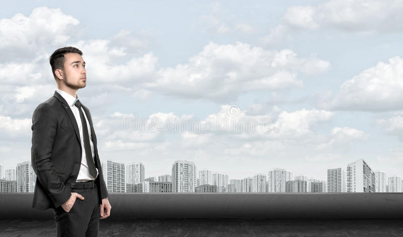 Young man in business suit, standing front of city landscape sunrise. Business, leadership and success concept royalty free stock image