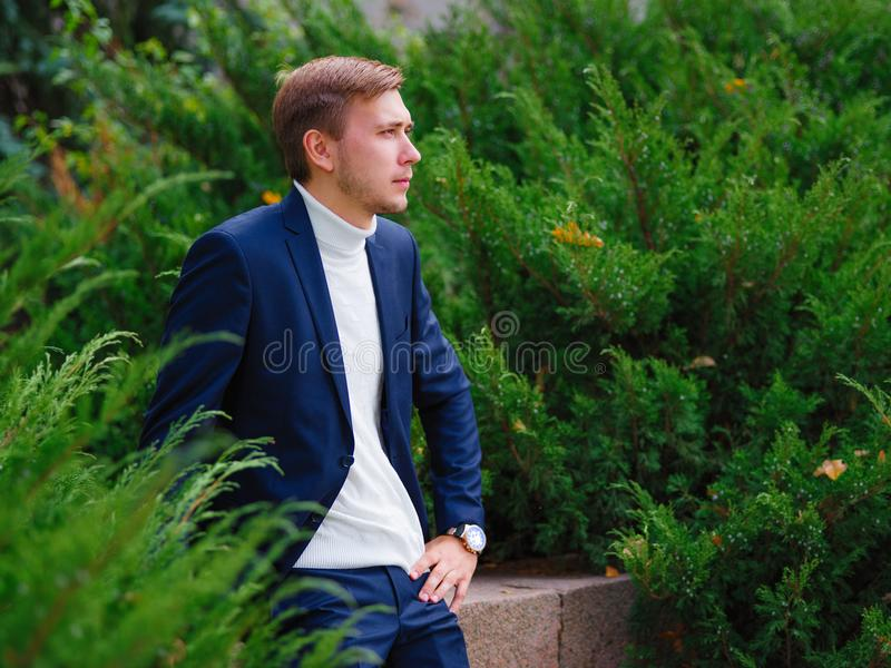 Young man, businessman in suit against the background of green Christmas trees. royalty free stock image