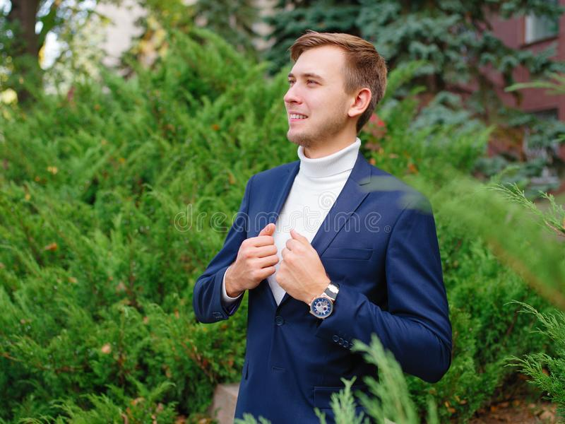 Young man, businessman in suit against the background of green Christmas trees. stock photography