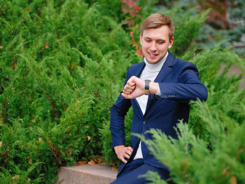 Young man, businessman in suit against the background of green Christmas trees. royalty free stock photography