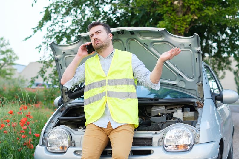 Young man calling the car service after a vehicle breakdown stock photo