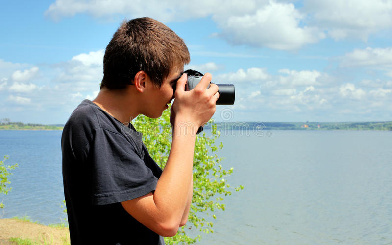 Young man with camera. Young man with digital photo camera aiming outdoor royalty free stock images