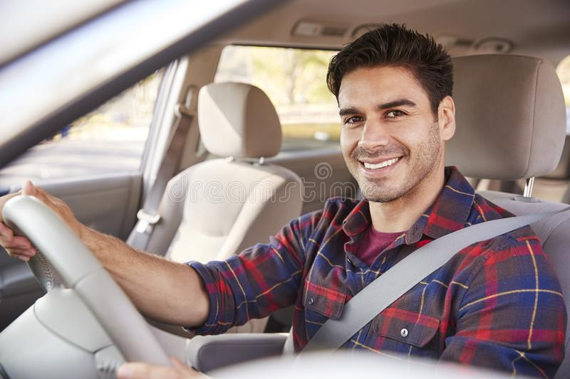 Young man in car driving seat looking to camera, portrait royalty free stock photography