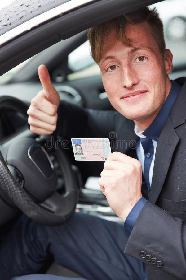 Young man in car holding drivers. Young happy man in car holding his new drivers license and his thumbs up royalty free stock photo